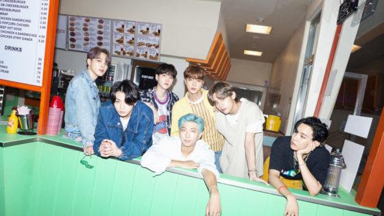 BTS Mitglieder stehend an einer Theke.